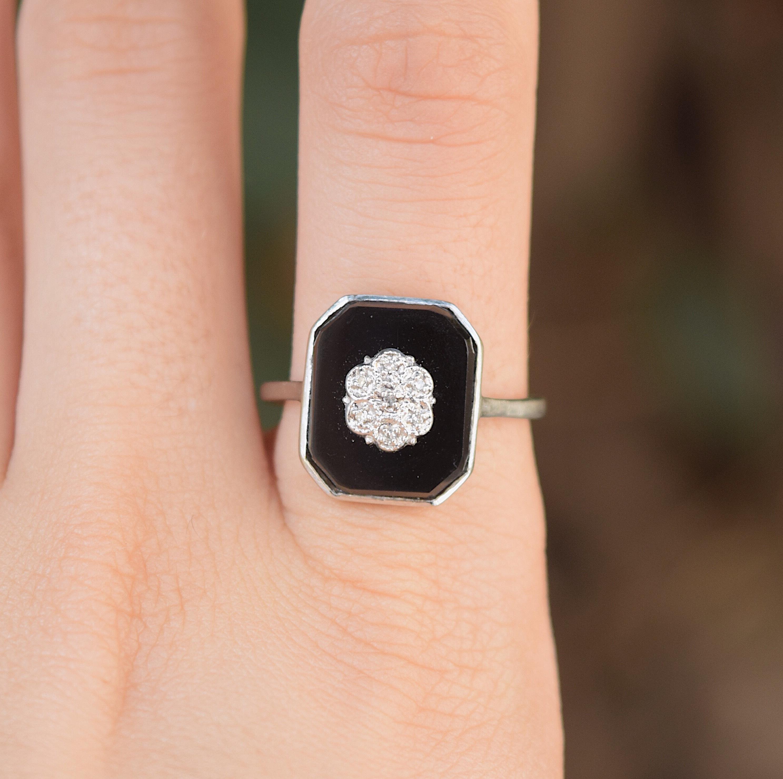 טבעת זהב עם אוניקס ועליו פרח משובץ ביהלומים קטנים.